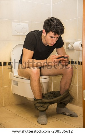 Young Dark Haired Man with Handheld Game or Cell Phone Sitting on Toilet with Pants Around Ankles - stock photo