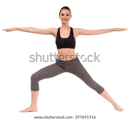 Young dark haired slim woman doing yoga exercise, stretching her arms to the side. - stock photo