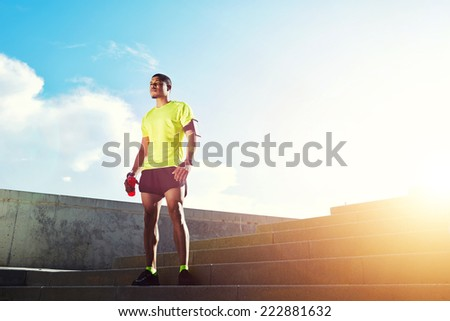 Young dark skinned jogger with muscular strong standing against soft sunset light outdoors, beautiful fit man in bright fluorescent sportswear, sports fitness concept - stock photo