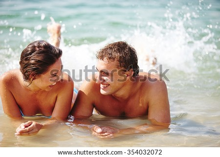 Young dates lying in water and looking at one another - stock photo
