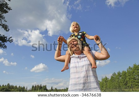 young daugther sitting on mothers shoulders