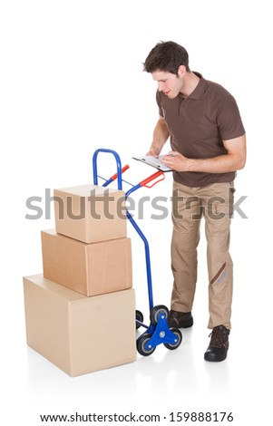 Young Delivery Man Holding Clip Board Standing With Stack Of Boxes - stock photo