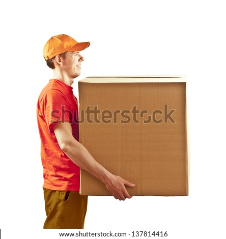 Young delivery man in red uniform holding the box on white background looking to the copy space area Space for inscription - stock photo