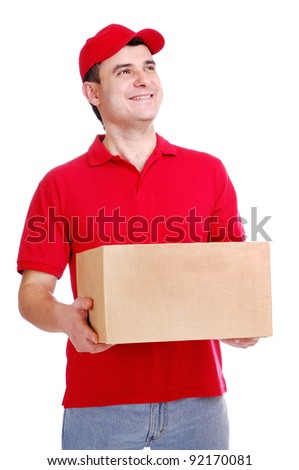 Young delivery man in red uniform holding the box on white background  looking to the copy space area