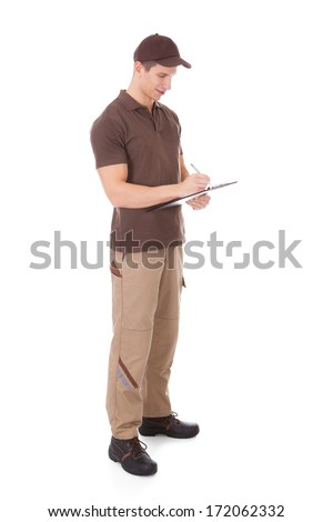 Young Delivery Man Writing On Clipboard Over White Background - stock photo