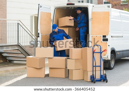 Young delivery men unloading cardboard boxes from truck on street - stock photo