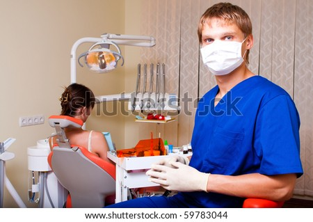 Young dentist in his office looking at the viewer - stock photo