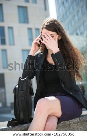 Young depressed business woman calling with mobile phone - negative expression