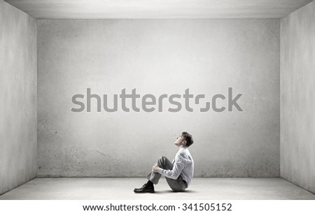 Young depressed businessman sitting on floor alone in empty room - stock photo