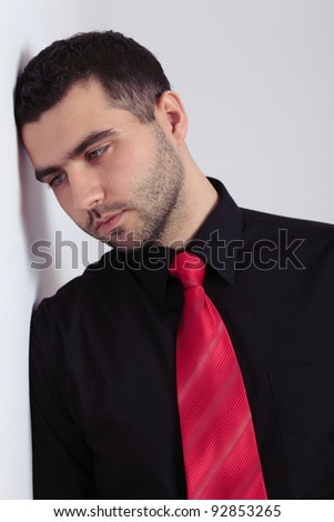 Young depressed man looks down, black shirt and red necktie - stock photo