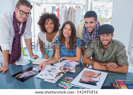 Young designers smiling at camera and working at desk