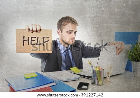 young desperate businessman holding help sign looking worried suffering work stress sitting at computer desk on grunge dirty background office in business project problem - stock photo