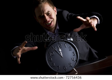 Young desperate businessman in dark suit at office desk jumping at alarm clock showing five minutes to twelve o'clock symbolizing the end is approaching, low-key image isolated on black background. - stock photo