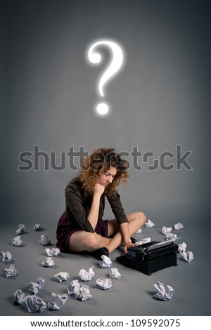 Young desperate girl writing with an old typewriter and question mark. Conceptual image.