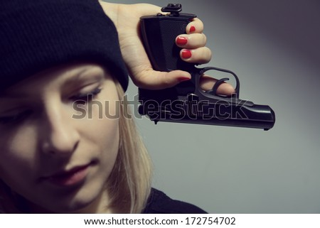Young desperate woman with a gun in his hand.