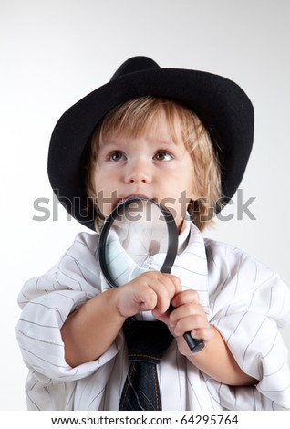 Young detective with magnifying glass, studio shot - stock photo