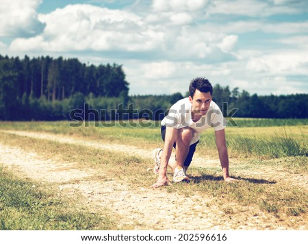 Young determined athletic man in the start position, ready to run on a path in a rural area, with green forest and field, outdoors, in a warm and cloudy summer day - stock photo