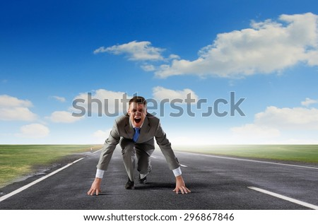 Young determined businessman standing in start position - stock photo