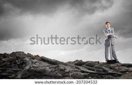 Young determined businessman with big hammer in hands standing on ruins