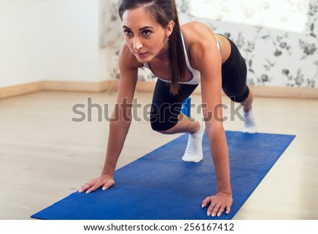 Young determined confident slim woman doing exercises on the blue mat looking straight forward - stock photo