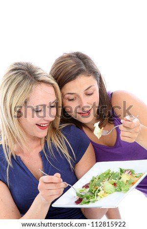 Young dieters sharing a salad Two attractive young female dieters sharing a fresh green leafy salad eating off the same plate as they keep on eye on one another in friendly comraderie - stock photo