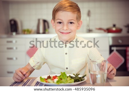 Young diligent boy  at a table eating healthy meal using cutlery