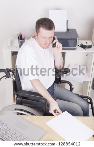 young disabled man in wheelchair working in a home Office.