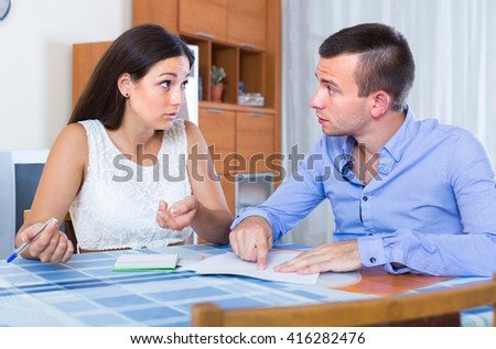 Young displeased couple quarreling at banking statement indoors