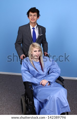 Young Doctor And Patient On Wheel Chair