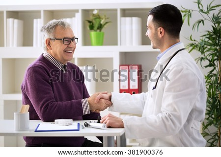 Young doctor congratulating senior patient on recovery - stock photo