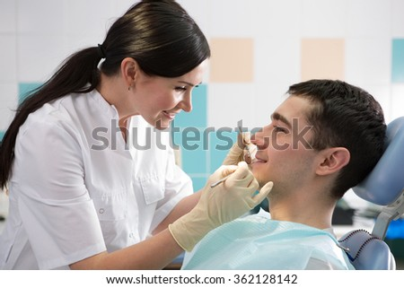 young doctor dentist examines the mouth of the patient - stock photo