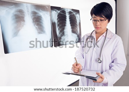 Young doctor describing results of X-Ray radiography - stock photo