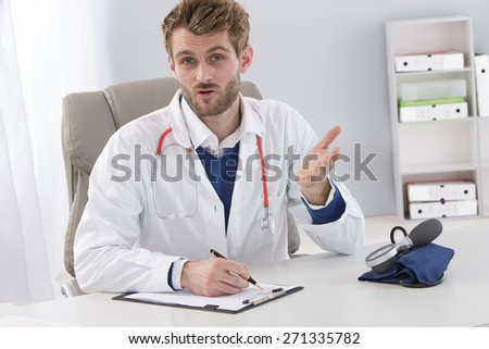 Young doctor explaining diagnosis to patient - stock photo