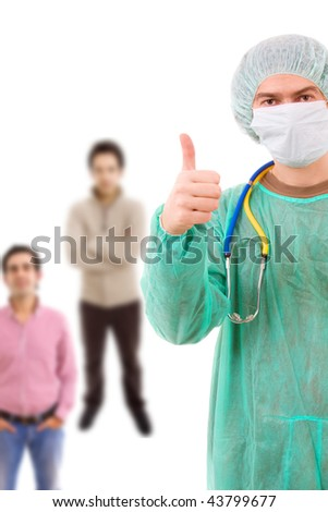 young doctor going thumb up with people standing in background - stock photo