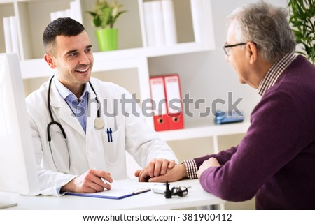 Young doctor holding hand and console his patient about disease - stock photo