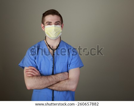 Young doctor in scrubs with a stethoscope and a mask looking confidently at the camera - stock photo