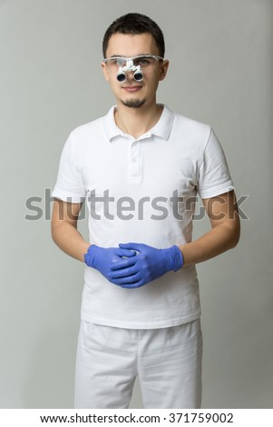 Young doctor in white uniform and blue latex gloves standing on the gray background and looking to the camera. He is holding his hands together. He has a dental binocular loupes on his face. Studio - stock photo
