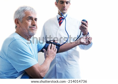 Young doctor measuring blood pressure to a senior man. Isolated on white background. - stock photo