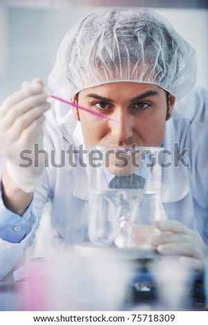 young doctor scientist in bright labaratory work research and  analyse content of  test tubes representing chemistry and research concept - stock photo