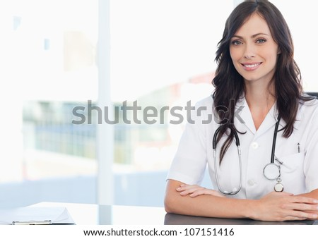 Young doctor sitting at the desk next to a clipboard - stock photo