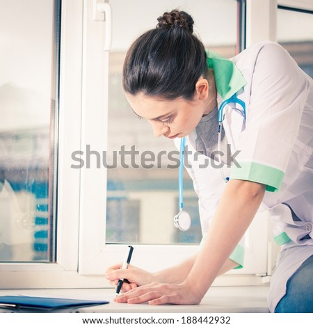 Young doctor sitting on window sill and writing