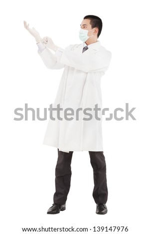 Young doctor standing and putting on his  gloves - stock photo