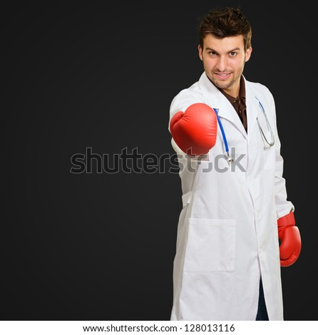 Young Doctor Wearing Boxing Gloves Giving Invitation On Black Background