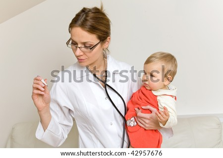 young doctor with baby  checking temperature with thermometer - stock photo