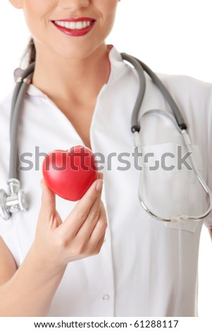 Young doctor with heart in her hand, isolated on white background - stock photo