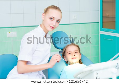 young doctor woman and girl in dentist office, regular visits to the dentist - stock photo