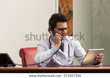 Young Doctor Working At His Computer While Talking On The Phone
