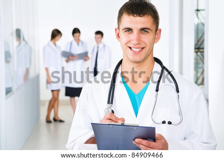 Young doctors are standing intside the hospital and looking at camera - stock photo