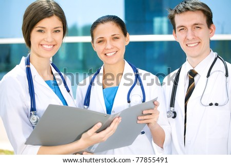 Young doctors are standing outside the hospital and looking at camera - stock photo