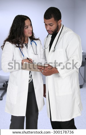 Young doctors in lab coats discussing a patient record - stock photo